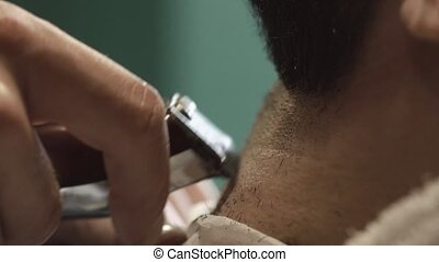 Barber hand cutting beard with clipper at barbershop. Close-up video, 4k. Barber works with the electric trimmer