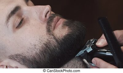 Barber hand cutting beard with clipper at barbershop. Closeup video, 4k. Barber works with the electric trimmer