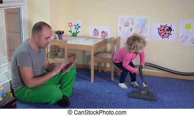 Father with tablet and cute girl clean floor with vacuum...
