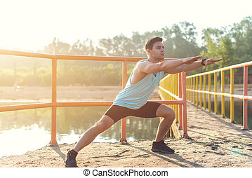 Fitness man athlete warming up legs before jogging outdoors.
