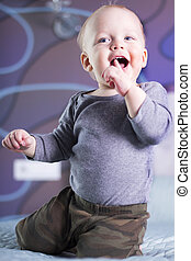 Playful funny baby boy sitting on the bed. Cute infant kid with a finger in his mouth