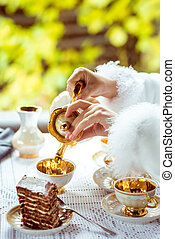 Side view of little beautiful girl's hands in the scenery of Alice in Wonderland pouring tea into a cup at the table