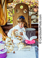Front view of an little beautiful girl in the scenery of Alice in Wonderland pouring tea into a cup at the table