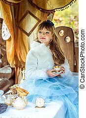 Front view of an little beautiful girl in the scenery of Alice in Wonderland holding a cup of tea at the table