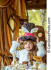 An little beautiful girl holding cylinder hat with ears like...