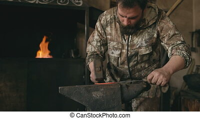 Young man blacksmith manually forging hot metal knife on...