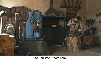 Young man blacksmith manually forging hot metal knife on anvil in traditional smithy