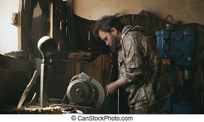 Bearded young man blacksmith manually polish metal knife on grinding machine in traditional smithy