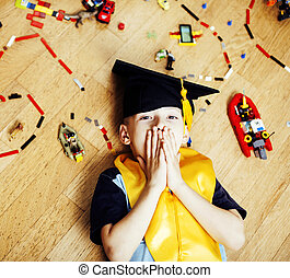 little cute preschooler boy among toys lego at home education in graduate hat smiling posing emotional, lifestyle people concept