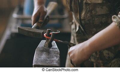 Closeup of blacksmith hands bending hot metal knife with...