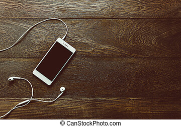 Top view white mo bile phone with earphones on office desk...
