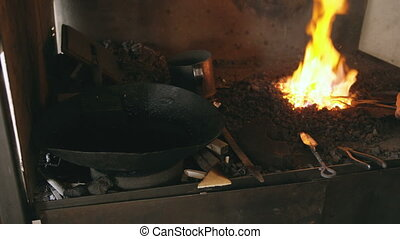 Closeup blacksmith manually temper steel knife in cold oil near fireplace in traditional smithy