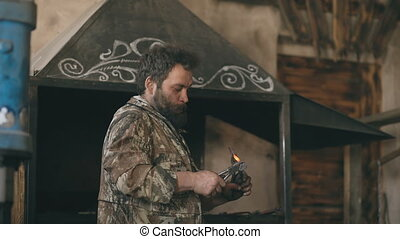 Bearded blacksmith bending hot metal knife with pliers and...