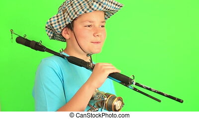 Boy posing with his fishing rod on chroma key green screen...