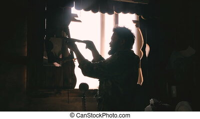 Silhouette of man blacksmith checking his knives made...
