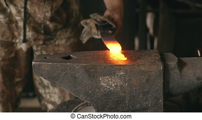 Slowmotion closeup blacksmith hands manually forging hot...