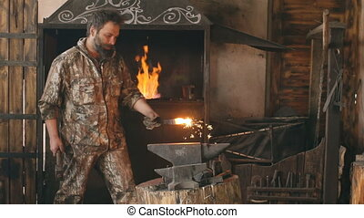 Slowmotion of bearded young man blacksmith manually forging...
