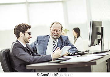 members of a business team discussing business documents in...