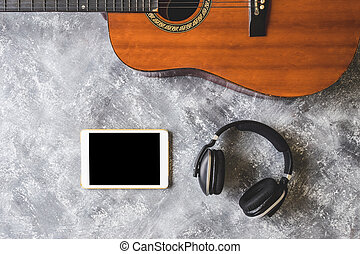 Top view of Guitar with headphone and tablet on grunge...