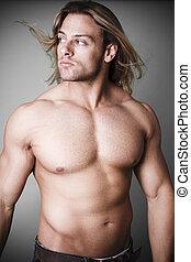 Muscular man measuring his waist - Muscular man standing...
