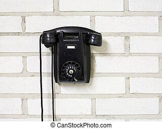 Telephone - Black bakelite telephone on a brick wall.