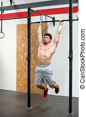 Bare chested man performing pulls ups