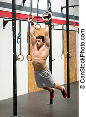Muscular man exercising on rings