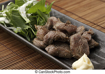 Black platter of sauteed beef with herbs