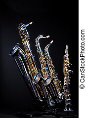 Four Saxophones on black - A set of four saxophones...
