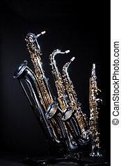 Four Saxophones on black - A set of four saxophones...