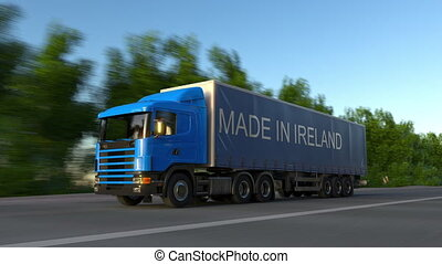 Speeding freight semi truck with MADE IN IRELAND caption on the trailer