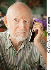 Grumpy senior man on telephone
