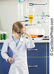 Little boy wearing lab coat in science laboratory