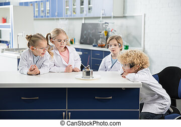 Kids in lab coats and protective glases making experiment in...