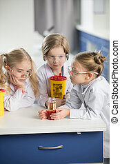 Kids in protective glasses making experiment in laboratory