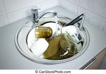 Many dirty dishes in the kitchen sink