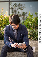 Asian Indian businessman using tablet pc outdoors, golden...