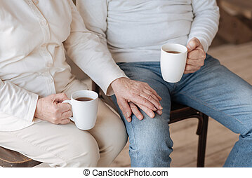 Close up of an elderly couple holding hands