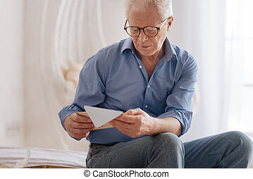 Moody cheerless man reading an old letter - Old memories....