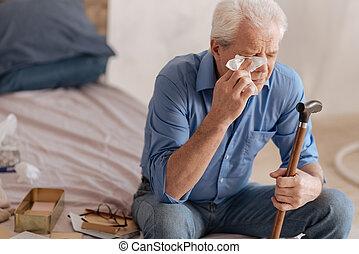 Depressed gloomy man wiping away his tears - So sad....