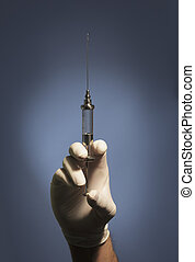 Just a little sting - A Hand holding an old syringe with a...