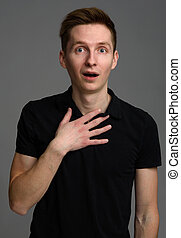 surprised casual young man portrait over gray background
