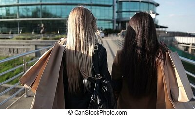 Shopaholic females walking on bridge at sunset - Closeup...