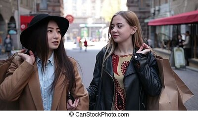 Multiracial female shoppers holding shopping bags