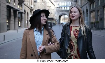 Multiethnic girlfriends shopping in city stores - Two...