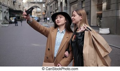 Happy women taking selfie after shopping on phone - Smiling...