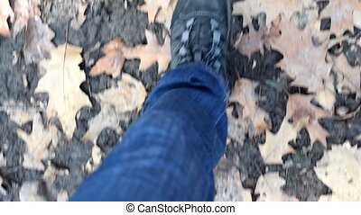 Feet of a person in jeans and hiking boots walking on ground