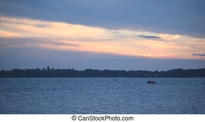Silhouette of a moving rubber boat at dusk on river during...