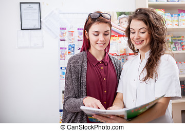 Pharmacist and her client looking at medical catalog