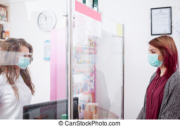 Pharmacist and her client with mask in front of the desk